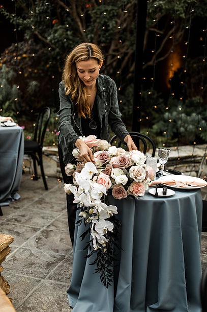 Gina Diaz arranging floral centerpiece