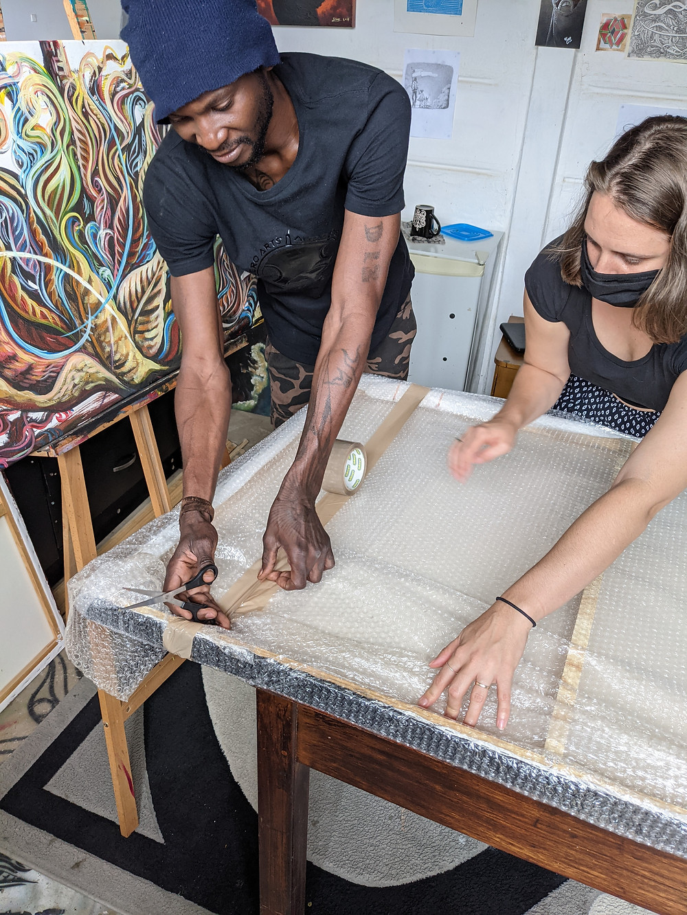 Petrus Amuthenu and Gina Figueira bubble wrap a large paining for travel. The work is for the Everyday Archive of Independence
