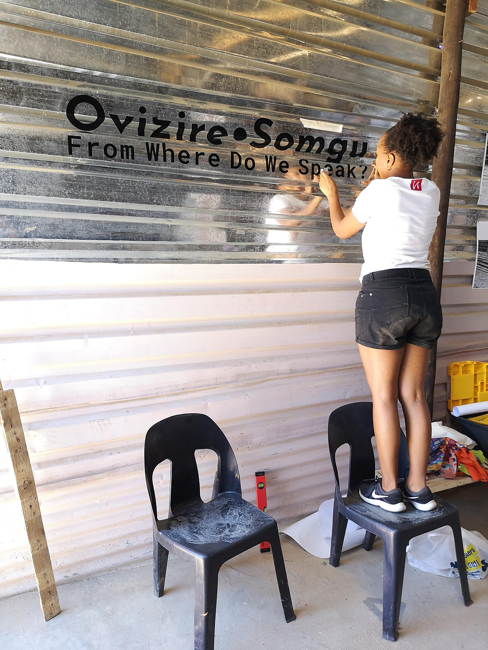 VitjituaNdjiharine install vinyl lettering on the wall of the Frans Nambinga Art Training Centre in Havana, Katutura, ahead of the opening 'Ovizire Somgu: From Where do we Speak'