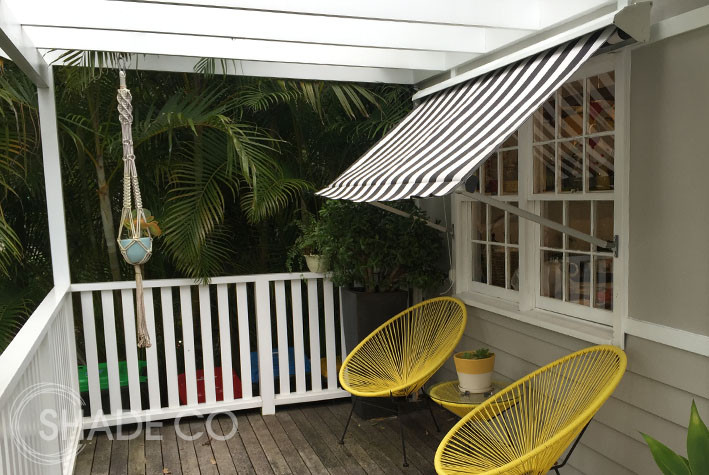 Pivot arm awning with pelmet and black and white striped fabric