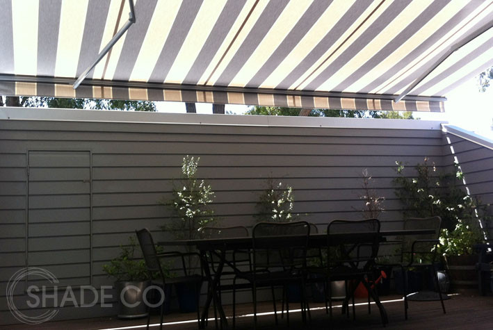Folding arm awning with striped fabric