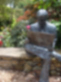 Brnze statue of a man sitting and reading the newspaper in a garden