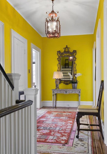 Bright yellow walls on landing in family home in Brooklyn designed by Jonathan Berger