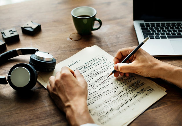 hands working on sheet music, a laptop, headphones and a cup of coffee