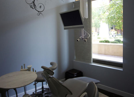 An image of a dental chair with television at Uptown Dentistry.