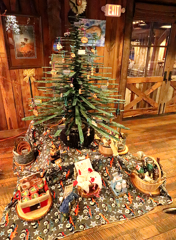 By #Be the Voice #Remember: Shannon & Larry Martell, Nancy & Wayne Yates, Jennifer Pfendler & Annie Young Sponsored by Philipsburg Rotary Club This handcrafted, all-wood tabletop Christmas tree brings to life Montana's rustic charm – with a little splash of redneck mixed in. Ornaments are made from driftwood, old shop pieces and parts, monster trucks, and more. This tree will also bring messages of hope, encouragement, and resources in support of suicide prevention and awareness.   $3,000
