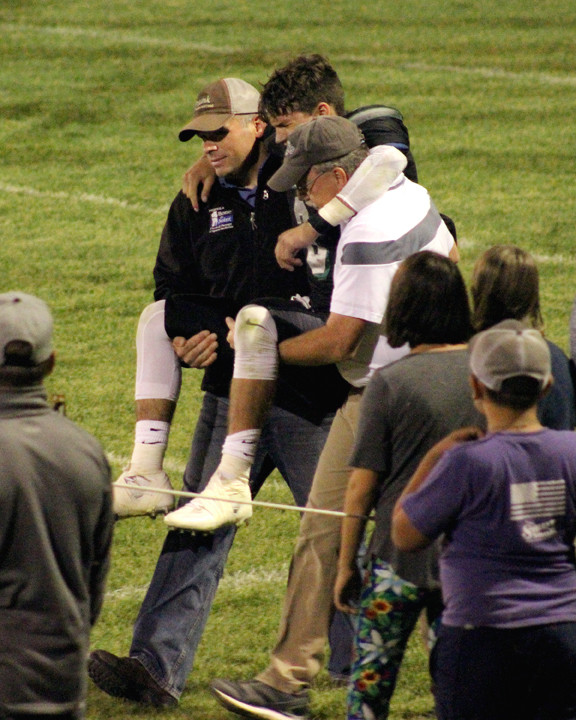 Titan player Mark Estes is carried from the field after a season-ending ACL injury.