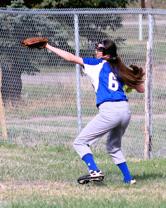 Sophia DeSantiago fields a ball at the fence and relays it back into the infield. (file photo)