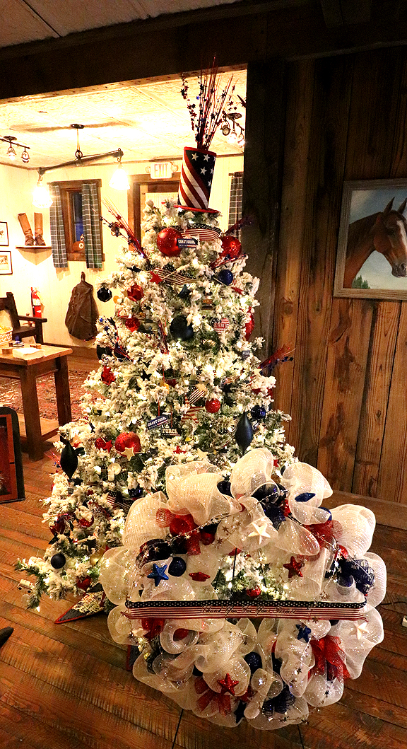 """By Christmas Emporium: Pat & Ed Siler, Michele & Craig Larson, Cheryl & Ron Locke, Rita Blankenship, Philipsburg Dental & Mary Beeam of Mary B's Quilts Sponsored by Granite Pharmacy  Our tree is a salute to service and says, """"Thank You"""" to all that have served and continue to serve the people of this great country. Includes a basket with wine, cheese and crackers along with hand- made napkins and a tabletop handcrafted floral display.  $1,200 / $1,000"""