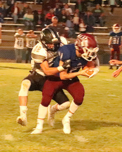 Tucker Weaver (32) registers his first QB sack of the season ion Clark Fork's Brian Mask.