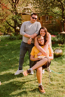 relaxed family photograph of three adult siblings in their garden in Bristol.