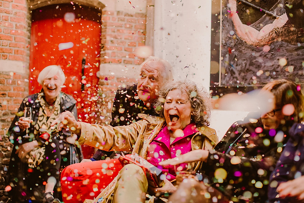a colourful confetti shot with guests laughing at a small wedding in Holland