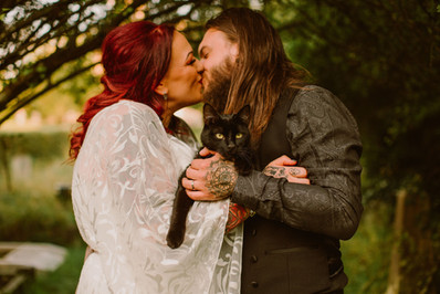 Alternative fun couple hold their cat as they kiss