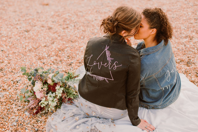Lesbian couple kiss whilst picnicing on the beach