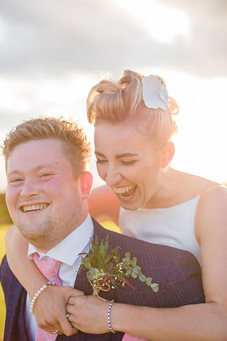 an alternative couple laugh together at their outdoor festival wedding in the UK