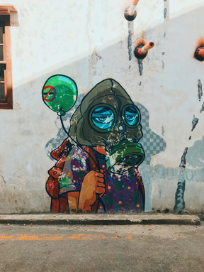 Photo of a building with graffiti wall art showing carton character wearing a gas mask and holding a green balloon painted with a no smoking symbol