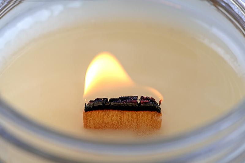 Scented candle crackling with wooden wick
