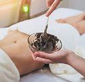 Beautiful woman in spa salon getting mud