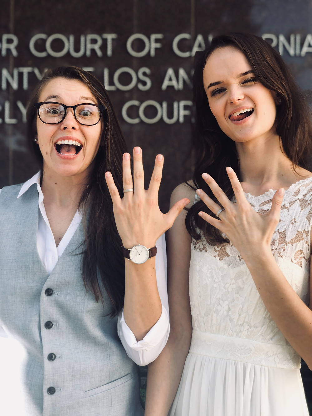 Two gay women showing off their wedding rings