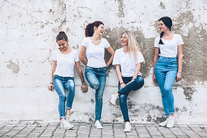 Group of four young diverse girls wearing blank white tshirt and jeans posing against rough street w