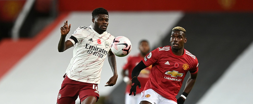 Arsenal's Thomas Partey is put under pressure by Paul Pogba [R] of Manchester United [Getty]
