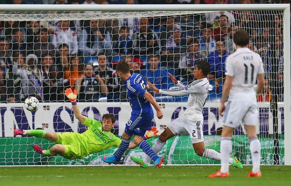 Klaas Jan Huntelaar of Schalke shoots past Iker Casillas.
