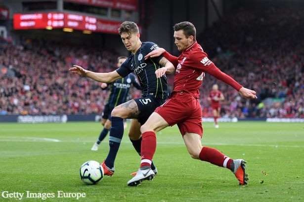 Andy Robertson and John Stones battle for the ball_.