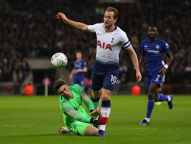 Harry Kane of Tottenham Hotspur is fouled by Kepa Arrizabalaga of Chelsea.