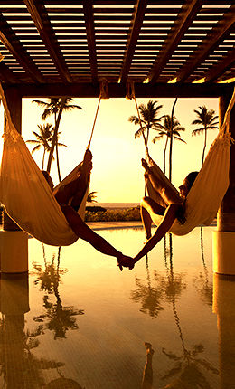 couple in hammocks holding hands