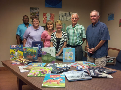 The Board of Trustee posing with books bought with the Constellation Community Champions Grant.