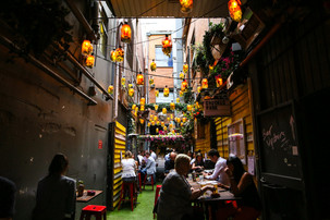 People enjoying their meals with family during the day under all of the light lamps in the laneway.