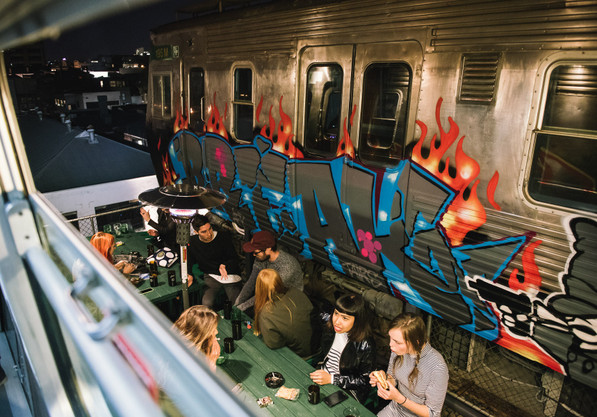 Easey's outdoor seating next to painted train with graffiti and long tables to sit at with lamp heaters.