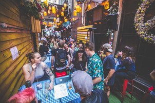 People networking and meeting at the outdoor tables of Chuckle Park, a hidden bar in a Melbourne laneway.