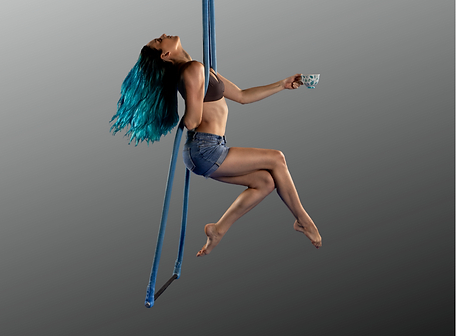Darcie Boatswain drinking tea while hanging from a trapeze