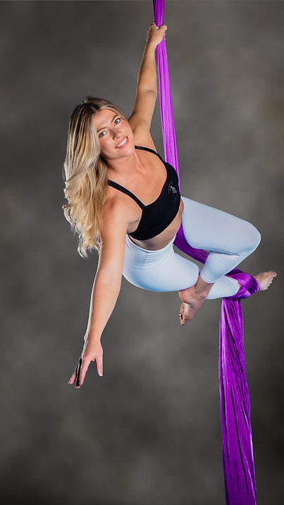 Girl smiling hanging from aerial silk