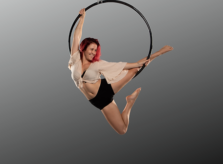 Ashley Hilderson smiling while suspended inside an aerial hoop