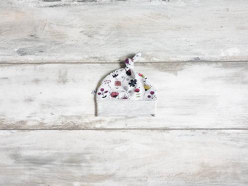 Cepurīte ar melnu un rozā ziedu rakstu ar mezgliņu