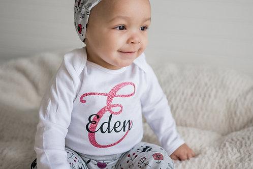 Bodijs ar bērna vārdu un rozā pirmo burtu