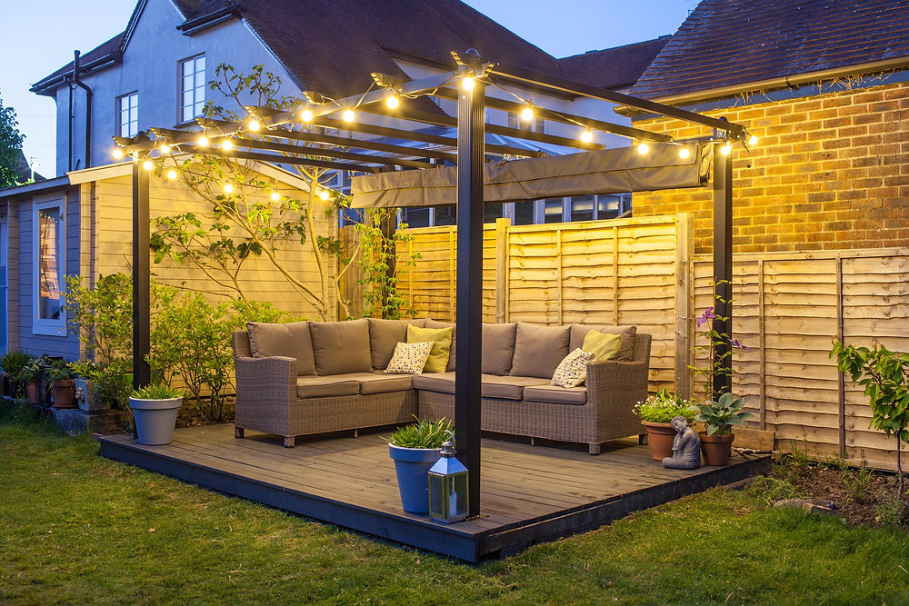 A contemporary pergola lit by festoon lights in a garden