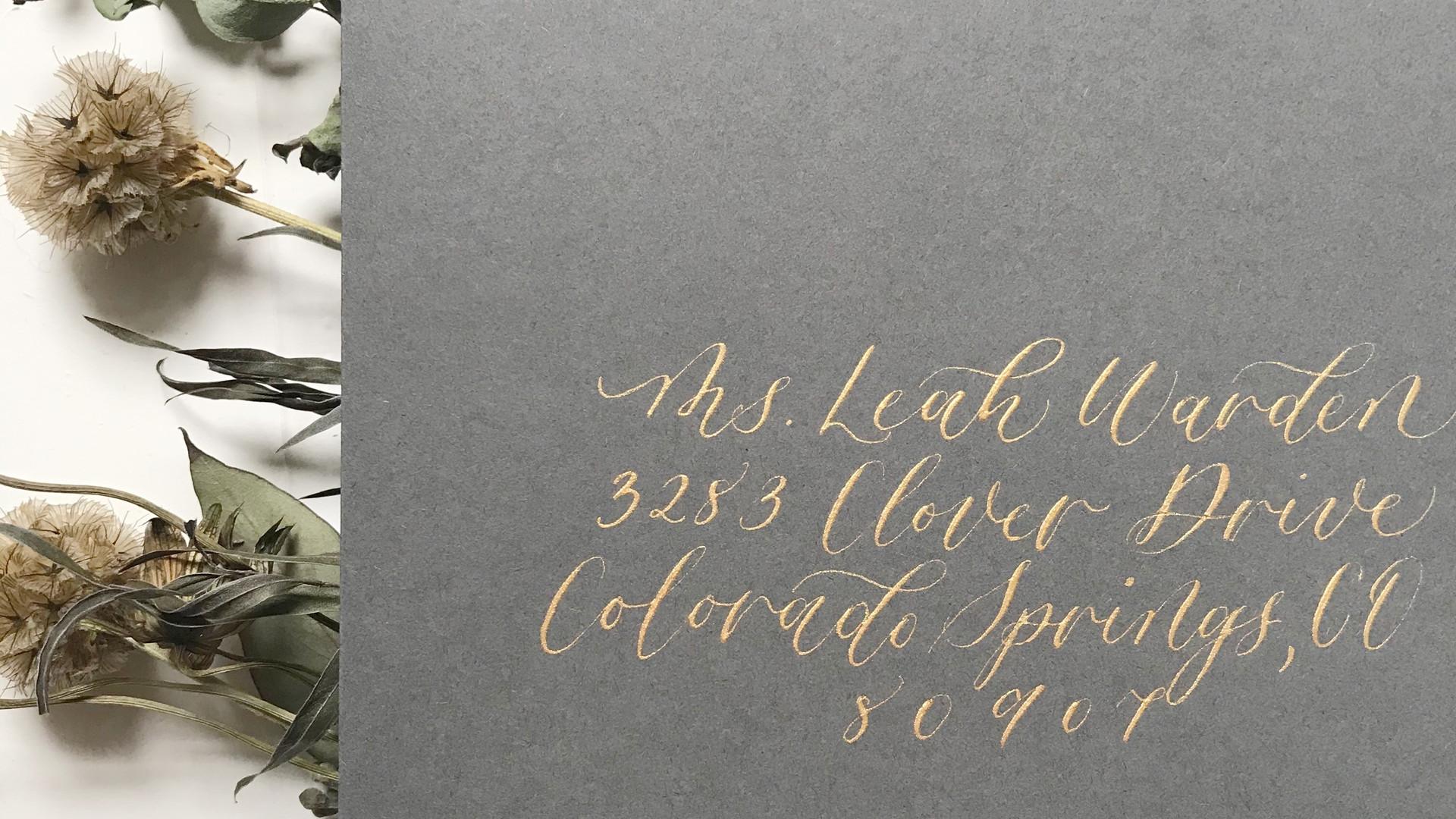 Gold ink calligraphy on dark grey envelope