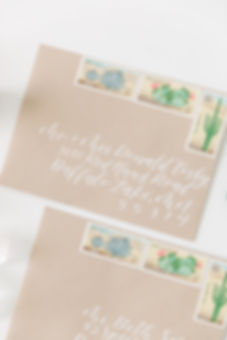 Kraft paper envelopes with white ink calligraphy addresses and vintage postage stamps for desert themed weddng
