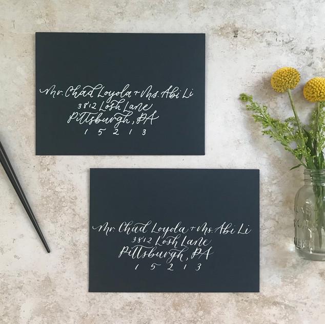 White calligraphy styles on navy blue envelopes