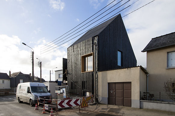 Bardage bois noir sur façade et toiture. Cadre fenêtre aluminium