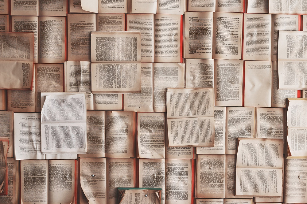 "<img src=""books.jpg"" alt=""open books scattered and pinned across a wall in different directions"">"