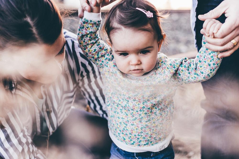 "<img src=""baby.jpg"" alt=""parents teaching their baby girl how to walk"">"