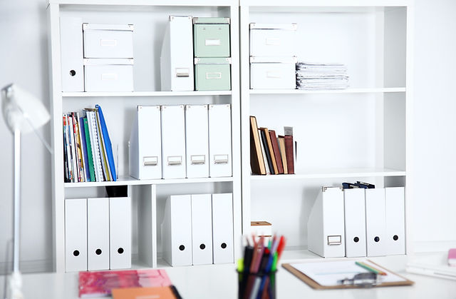 Image of the center of two white bookcases filled with books, binders, and notebooks