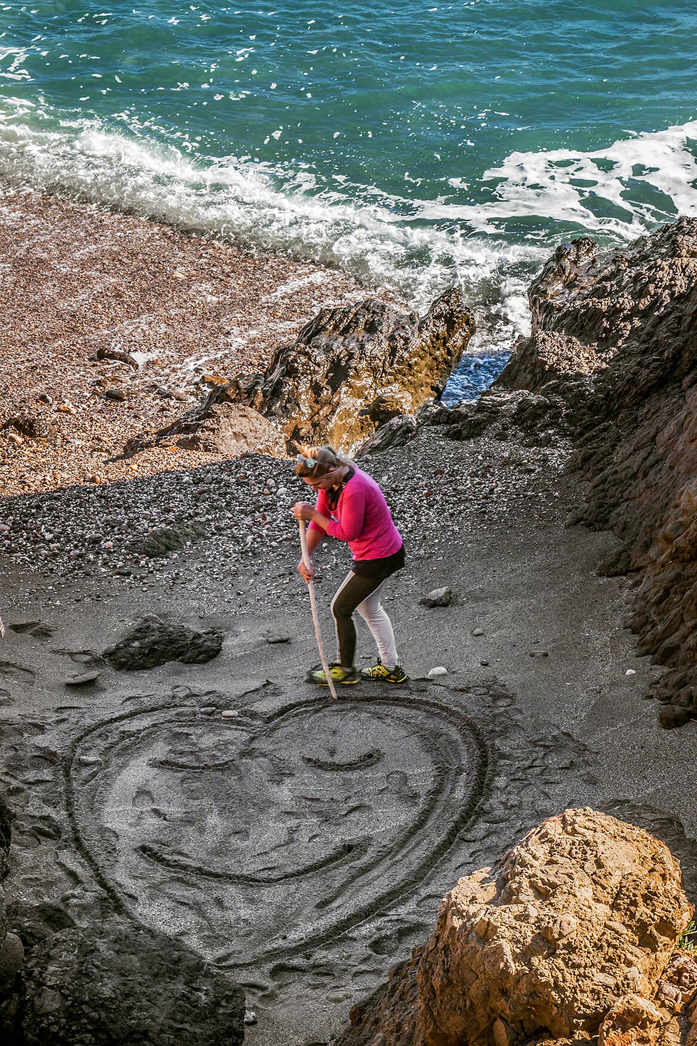 Woman drawing a heart in the sand at a beach in Almeria, Spain