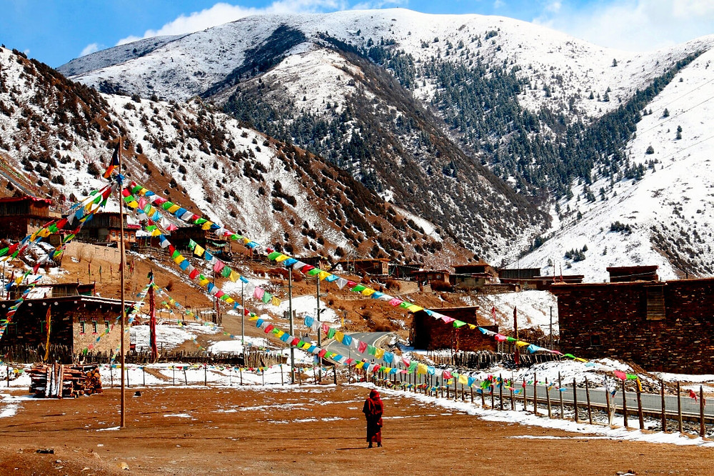A Tibetan monk in the snow mountains landscape