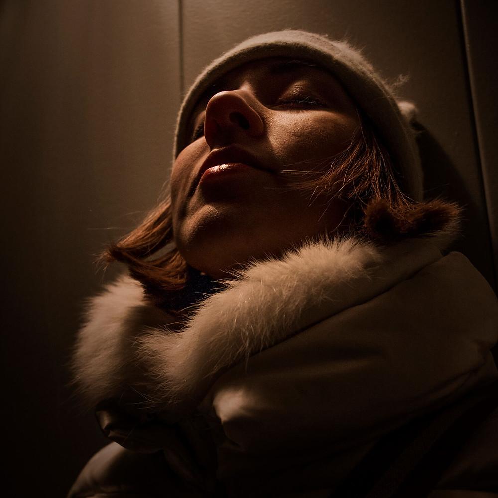 Chica meditando con ojos cerrados y ropa de invierno y gorro en ascensor
