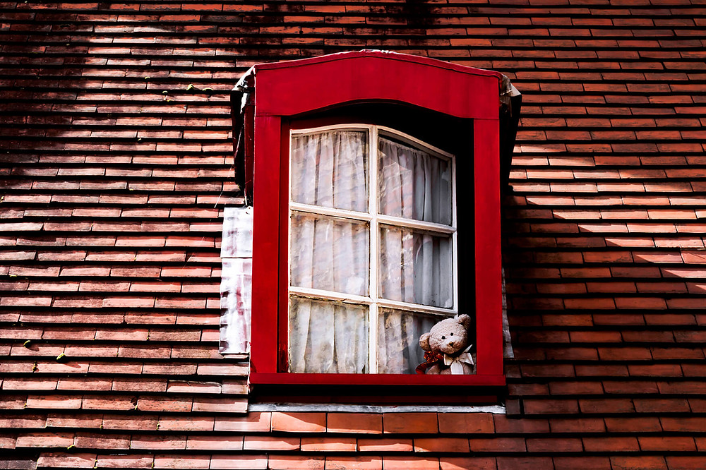 osito de peluche ventana roja tejado